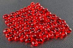 Rote Kapseln der Tablets in der Masse, mit einer Schärfentiefe Bild Lizenzfreie Stockfotos