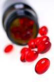 Rote Kapseln und Medizinflasche Stockfotos