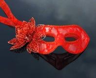 Rote Karnevalsmaskerademaske, die auf schwarzer Tabelle liegt Stockbilder