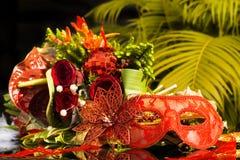 Rote Karnevalsmaskerademaske mit Blumenstrauß des neuen Jahres Lizenzfreie Stockbilder