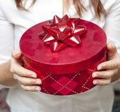 Rote Kastenholding in der Hand des jungen Mädchens Lizenzfreies Stockfoto