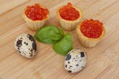 Rote Kaviar Tartlets, Eier auf dem hölzernen Hintergrund Lizenzfreie Stockfotografie