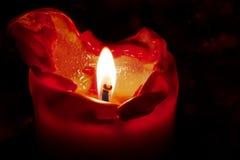 Rote Kerze mit Flamme und schmelzendem Wachs gegen einen dunklen Hintergrund Stockbilder
