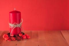 Rote Kerze mit roten Oberteilen Stockfoto