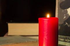Rote Kerze und einige alte Bücher Lizenzfreies Stockbild