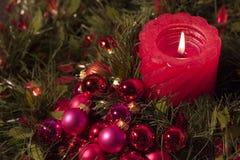 Rote Kerze- und Weihnachtskugeln Stockfoto