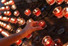 rote Kerzen beleuchtet und die Hand des Kindes Stockfotografie