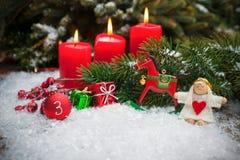 Rote Kerzen, die im Schnee für dritte Einführung brennen Lizenzfreie Stockfotografie