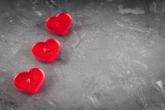 Rote Kerzen in Form von Herzen auf einem grauen Hintergrund Das symb Stockfotos