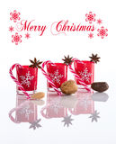Rote Kerzen, Kerzenhalter mit Kristallschneeflocken, Zuckerrohre, Anissterne und Nüsse, lokalisiert auf reflektierendem weißem Pl Stockfotos