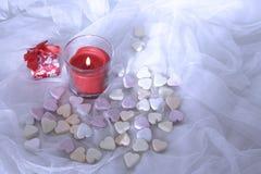 Rote Kerzen-, rosa und weißesüßigkeiten auf weißem Satinhintergrund, Valentinsgruß ` s Tageskonzept Lizenzfreies Stockbild