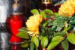 Rote Kerzen und künstliche Blumen auf einem Grab stockbilder
