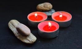 rote Kerzen und Steine auf schwarzem Hintergrund Stockfoto