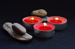 rote Kerzen und Steine auf schwarzem Hintergrund Stockbilder