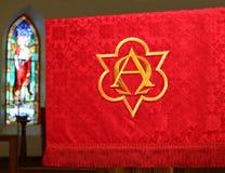 Rote Kirchenfahne vor undeutlichem Buntglasfenster stockfotos