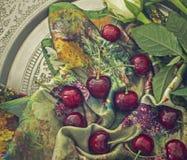 Rote Kirschen auf einem bunten Schal Stockfotos