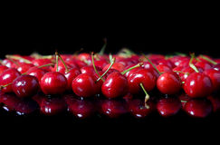 Rote Kirschen auf schwarzem Hintergrund lizenzfreie stockfotos
