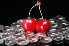 Rote Kirschen und Glaskorne Stockfotos