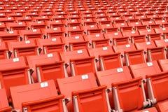 Rote Klappstühle gezeichnet auf dem Stadionssport Stockfoto