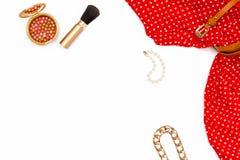 Rote Kleiderfrauen, Make-upbürste, Perlenarmband und anderes Zubehör auf einem weißen Hintergrund Minimales Konzept der weibliche Stockfoto
