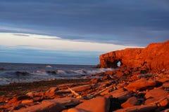 Rote Klippen auf Prinzen Edwards Island bei Sonnenuntergang stockfotos