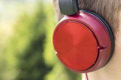 Rote Kopfhörer auf dem Kopf eines Jugendlichen stockbilder
