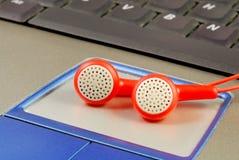 Rote Kopfhörer auf einem Laptop Lizenzfreie Stockfotografie