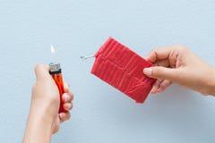 Rote Kracher und ein Feuerzeug in der Hand Lizenzfreies Stockfoto