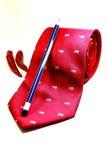 Rote Krawatte mit symbolischem Ausdruck des Bleistifts und des Paprikas der Stimmung Lizenzfreies Stockfoto
