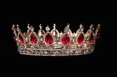 Rote Krone mit den roten Edelsteinen lokalisiert auf schwarzem Hintergrund Lizenzfreie Stockfotos