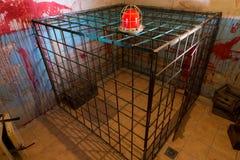 Rote Lampe auf dem Eisenkäfig im Keller mit Blut plätscherte Wand Stockfotografie