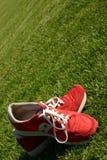 Rote laufende Schuhe auf einem Sportfeld Lizenzfreies Stockfoto