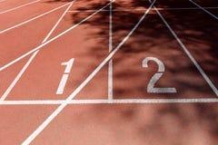 Rote Leichtathletikbahn im Schatten, srgb Bild Stockfotos