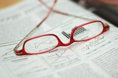 Rote Lesegläser auf Handelszeitung Stockfotografie