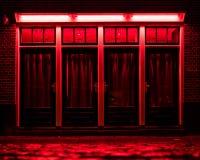 Rote Leuchte-Bezirk in Amsterdam Rote Kästen mit Vorhängen und nass Kopfsteinen auf der Straße stockfoto