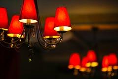 Rote Leuchter auf der Decke mit fünf Haubenlampen stockfoto