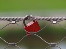 Rote Liebe schloss das Hängen an einem Zaun stockbild