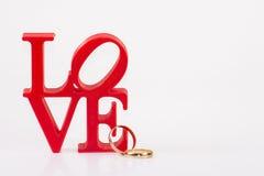 Rote Liebesbriefe auf weißem Hintergrund auf dem links mit zwei Ringen lizenzfreie stockfotos