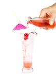 Rote Limonade mit Partystroh in der Hand auf Weiß Stockfotografie