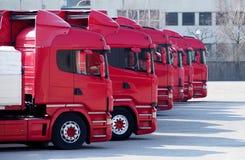 Rote LKWs richteten in einem Parkplatz eines Transportes aus und Reederei, bereiten vor, um zu gehen Stockfotos