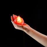 Rote lodernde Kerze in der Hand Stockfotos