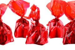 Rote Luxuxbonbons in der Zickzackreihe getrennt auf Weiß Stockfotos