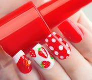 Rote Maniküre der Sommerart mit Erdbeeren und Tupfen stockfotos