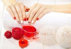 Rote Maniküre mit dekor Badekurort lizenzfreies stockbild