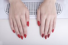 Rote Maniküre mit einem Muster Weibliche Hände im Maniküresalon lizenzfreie stockbilder
