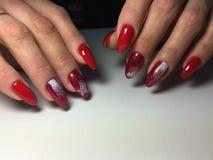 rote Maniküre mit weißen Schneeflocken auf langen Nägeln stockfoto