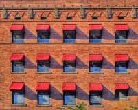 Rote Markisen auf Art Deco Brick Building lizenzfreies stockbild