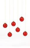 Rote matte Weihnachtsbälle, die an den goldenen Schnüren auf weißem Hintergrund hängen Lizenzfreies Stockbild
