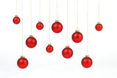 Rote matte Weihnachtsbälle, die an den goldenen Schnüren auf weißem Hintergrund hängen Lizenzfreies Stockfoto