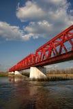 Rote Metallüberfahrtbrücke benutzt durch Züge, um über einen großen Fluss zu gehen Lizenzfreie Stockbilder